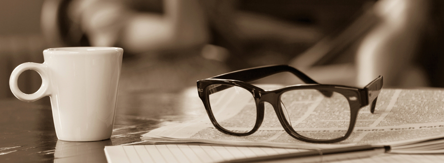 eyeglasses sit on newspaper with cup of coffee.
